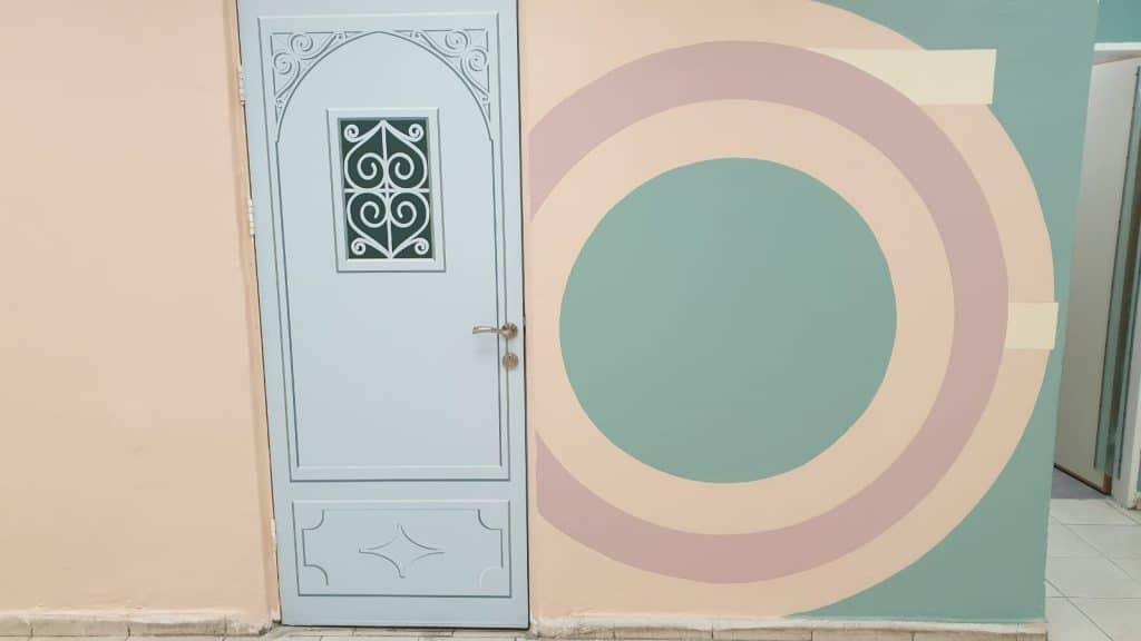תקריב של דלת על רקע ציור גאומטרי