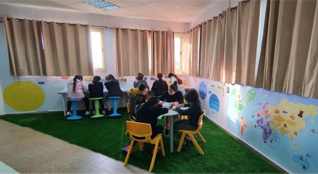 ילדים לומדים בבית ספר ניצן כיתה אלטרנטיבית שולחנות מחיקים כיסאות תנועה